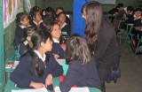 Girls in school uniform talking together in a classroom