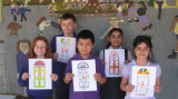 Children holding up colourful 'door' artwork